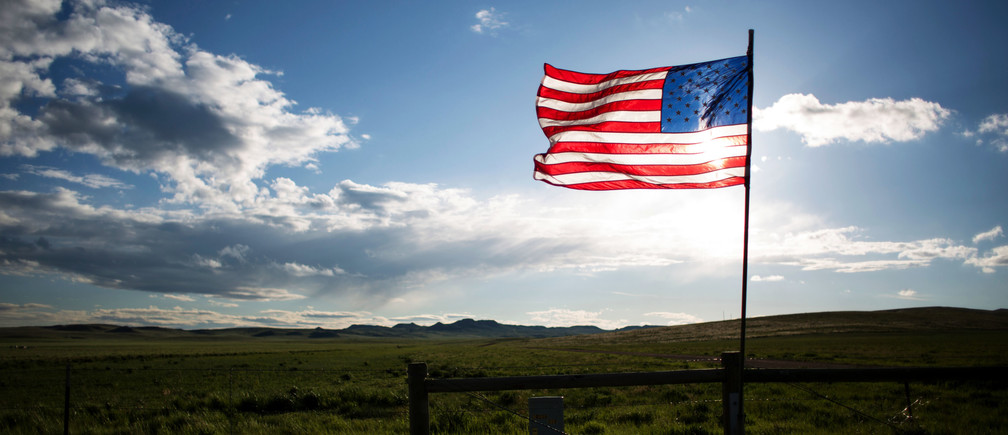 An American flag is seen along Wyoming Highway 59 near a residential housing development south of Gillette, Wyoming, U.S. May 31, 2016.  REUTERS/Kristina Barker - RTSXKMM