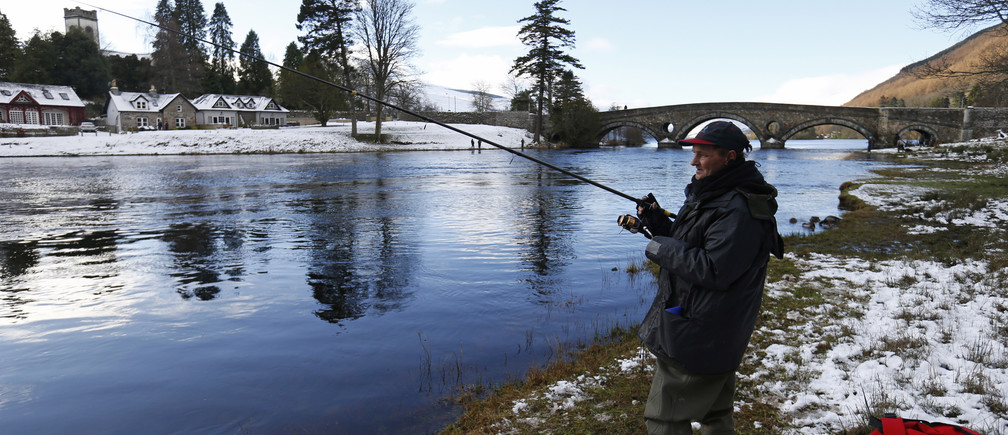 An angler fishes on the opening day of the salmon fishing season on the River Tay at Kenmore in Scotland, Britain January 15, 2016. REUTERS/Russell Cheyne - RTX22J9O