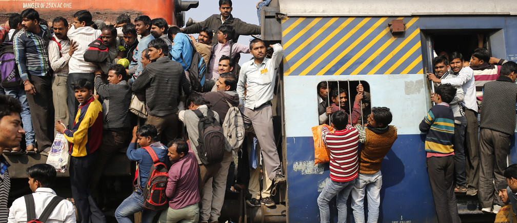 Passengers board an overcrowded train near a railway station at Loni town in the northern state of Uttar Pradesh, India, February 24, 2016. India's federal-run railways will have to depend on more government support and borrowing to fix their finances in its budget on Thursday, with New Delhi reluctant to unveil steep fare hikes ahead of key state elections, officials said. REUTERS/Anindito Mukherjee - D1AESOWINXAA