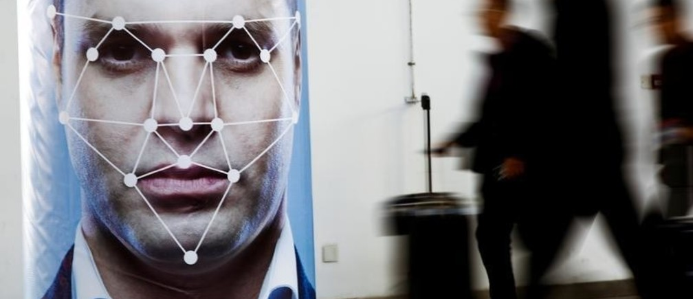 People walk past a poster simulating facial recognition software at the Security China 2018 exhibition on public safety and security in Beijing, China October 24, 2018.   REUTERS/Thomas Peter - RC1318930250