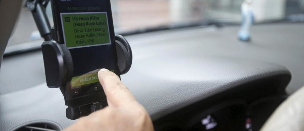 A GrabTaxi touches on his smartphone to check the bill for a customer in Hanoi, Vietnam, September 9, 2015. A young, tech-savvy population short on cars but big on smartphones is driving double-digit growth for ride-hailing apps Uber and GrabTaxi in Vietnam, and inspiring some executives to dream of replacing private car ownership altogether. Ride-sharing apps have taken off among Vietnam's rapidly expanding middle class as they provide four-wheeled comfort in a country better known for chaotic swarms of scooters and Southeast Asia's most expensive taxi fares. Picture taken September 9, 2015. REUTERS/Kham - GF10000199983