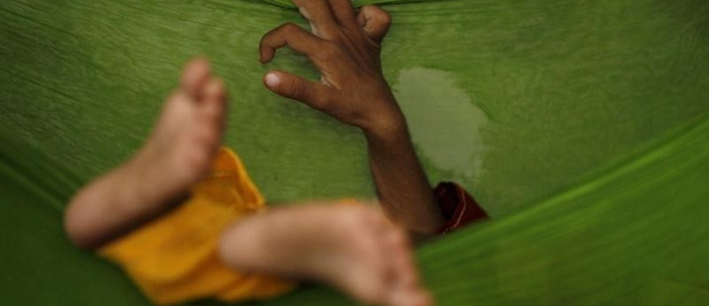 A two-year-old malnourished boy sleeps in a hammock while taking refuge with his family in a classroom in Sukkar, in Pakistan's Sindh province August 13, 2010. Disease outbreaks pose new risks to victims of Pakistan's worst floods in decades, aid agencies said on Friday, potentially hindering already complicated relief efforts. The floods, triggered by torrential monsoon downpours, have engulfed Pakistan's Indus river basin, killing more than 1,600 people, forcing two million from their homes and disrupting the lives of about 14 million people, or 8 percent of the population. REUTERS/Akhtar Soomro (PAKISTAN - Tags: DISASTER ENVIRONMENT) - GM1E68D1H3H01