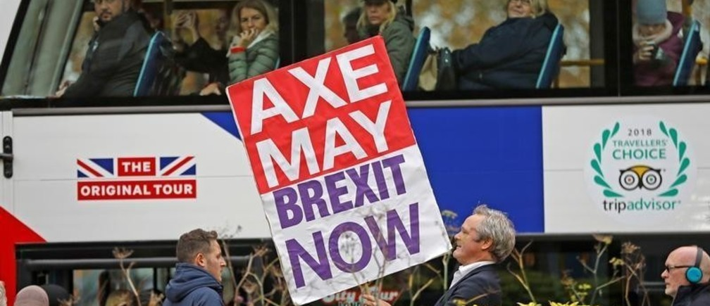 A pro-Brexit campaigner holds a placard as a tourist bus passes by in Westminster London, Britain, November 16, 2018. REUTERS/Peter Nicholls - RC1B71EFE970