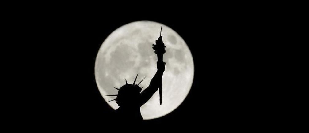 The rising supermoon is seen behind a statue on top of the Natural History Museum in Vienna, Austria November 14, 2016