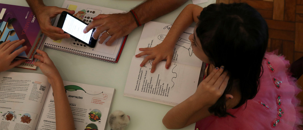 Alice, 5, watches a video sent by school as she studies at home with her father during a lockdown in Santo Andre, Brazil.