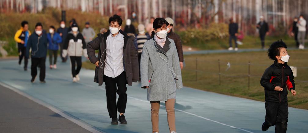 Personas con máscaras para evitar la propagación de la enfermedad coronavirus (COVID-19) caminan por una pista mientras se ejercitan en un parque de Seúl, Corea del Sur, el 24 de abril de 2020.
