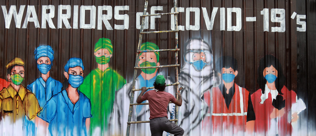 A man gets off a ladder as he completes a mural paying tribute to 'COVID-19 warriors' as India eases lockdown restrictions that were imposed to slow the spread of the coronavirus disease (COVID-19), in New Delhi, India, June 8, 2020. REUTERS/Anushree Fadnavis     TPX IMAGES OF THE DAY - RC2X4H9288EP