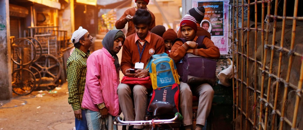 A schoolboy shows his mobile phone to a rickshaw puller takign him and other students to school on a cold winter morning in the old quarters of Delhi January 30, 2014.