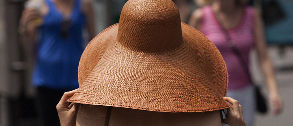 A woman covers herself with a large hat in Times Square during a heat wave in Manhattan, New York, July 19, 2013.