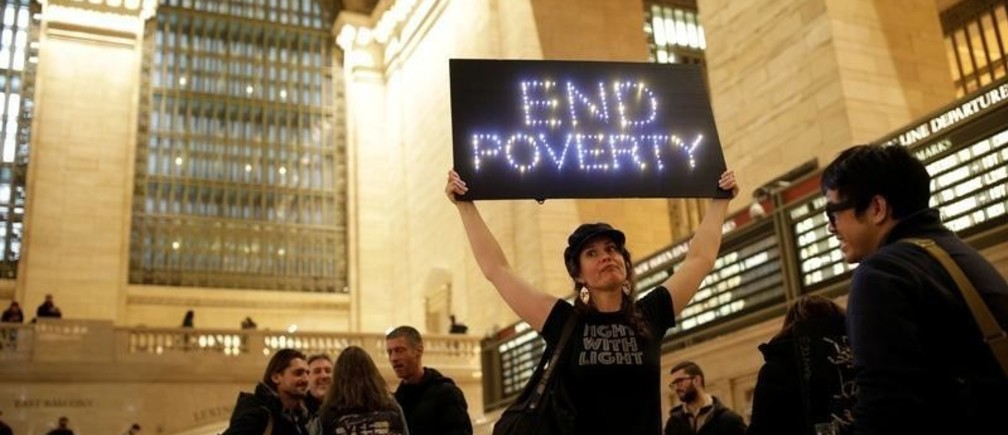 """A female demonstrators holds an """"End Poverty"""" light up sign during Non-March for Disabled Women hosted by Rise and Resist with help from the Women's March NYC in Grand Central Station in the Manhattan borough of New York City, New York, U.S., January 19, 2019. REUTERS/ Jose Alvarado Jr. - RC18D09D4F00"""