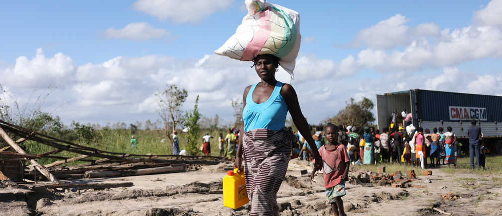 A Women walks after receiving parcel from an aid organisation after Cyclone Idai, near Dondo village outside Beira, Mozambique, March 24, 2019. REUTERS/Siphiwe Sibeko - RC136D4D9B70