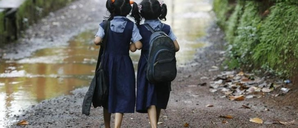 Seven year old twins Shahana (R) and Shahala (L)  walk to their school in Kodinji village in the southern Indian city of Kerala July 28, 2009.  Kodinji, with around 2,000 families, has at least 204 pairs of twins, according to survey by Twins and Kins Association (TAKA), a voluntary organisation. Picture taken July 28, 2009. REUTERS/Arko Datta (INDIA EDUCATION SOCIETY)