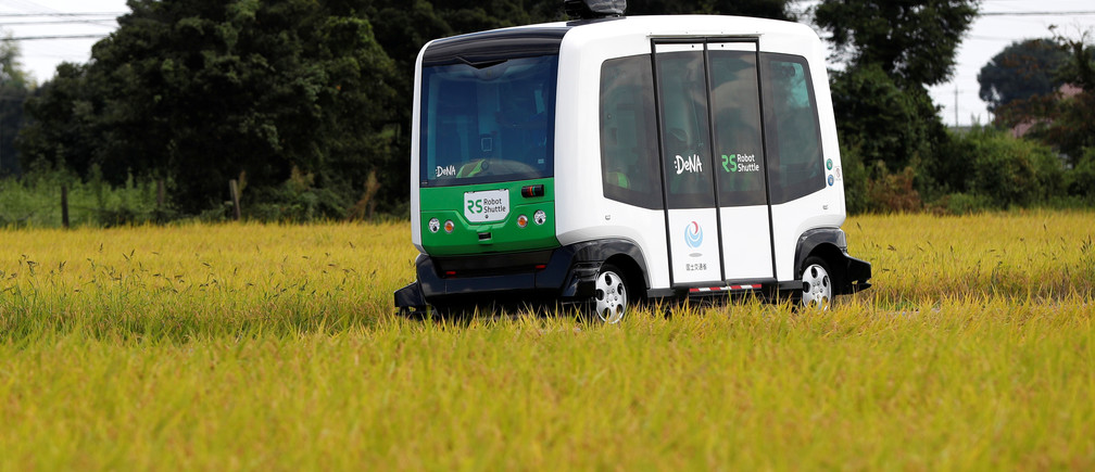 Robot Shuttle, a driver-less, self driving bus, using software developed by Japan's internet commerce and mobile games provider DeNA Co., drives past between rice stalk during an experimental trial with a self-driving bus in a community in Nishikata town, Tochigi Prefecture, Japan September 8, 2017. Picture taken September 8, 2017.     REUTERS/Issei Kato - RC1B9E71DC30