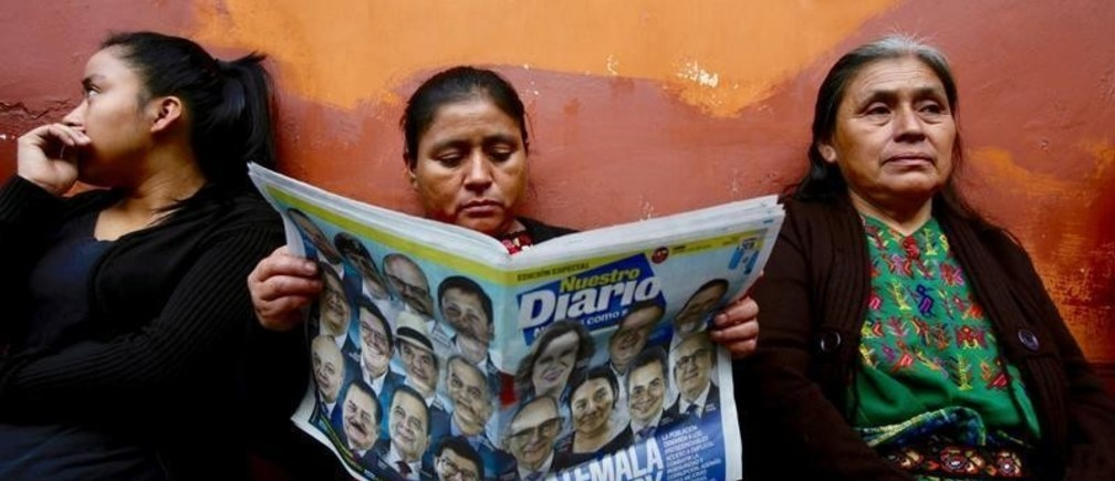 A woman reads a newspaper as she stands in a queue outside a polling station during the first round of presidential election in Guatemala City, Guatemala, June 16, 2019. REUTERS/Saul Martinez     TPX IMAGES OF THE DAY - RC19AA5FF880