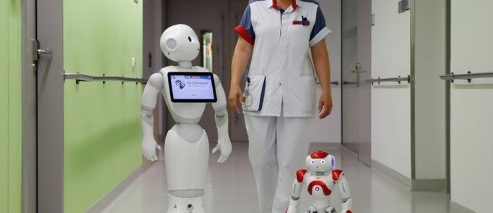 "A nurse walks with ""Pepper"" (L) and ""Zora"" the robots, humanoid robots designed to welcome and take care of visitors and patients, at AZ Damiaan hospital in Ostend, Belgium June 16, 2016. REUTERS/Francois Lenoir"