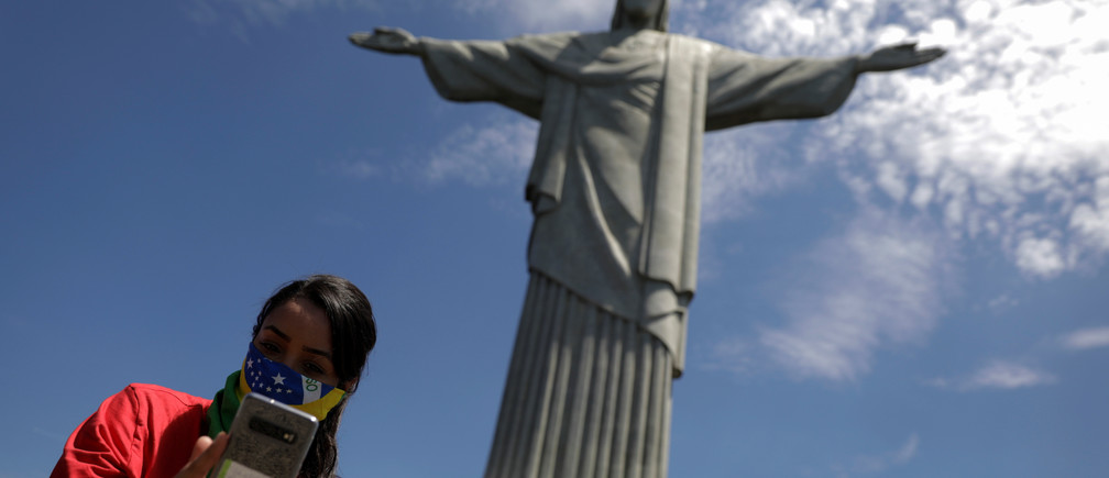 A tourist takes a selfie as she uses a Brazilian flag as a protective face mask, during a visit to Christ the Redeemer statue after reports of coronavirus in Rio de Janeiro, Brazil, March 16, 2020. REUTERS/Ricardo Moraes - RC27LF95AVY7