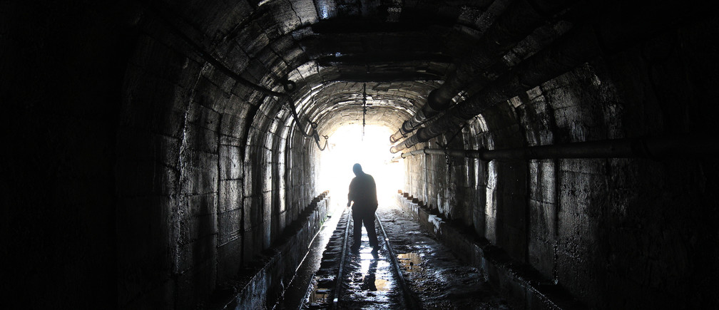 A mine worker is silhouetted as he walks inside a tunnel at the Kilembe mines, in the foothills of the Rwenzori Mountains, 497km (309 miles) west of Uganda's capital Kampala, January 31, 2013. The Kilembe copper-cobalt mine operated from 1956 to 1972, when it closed due to a drop in world copper prices and now lay in ruins. Uganda's President Yoweri Museveni has promised to rehabilitate the Kilembe mines. REUTERS/James Akena (UGANDA - Tags: ENVIRONMENT BUSINESS COMMODITIES EMPLOYMENT) - GM1E92103TH01