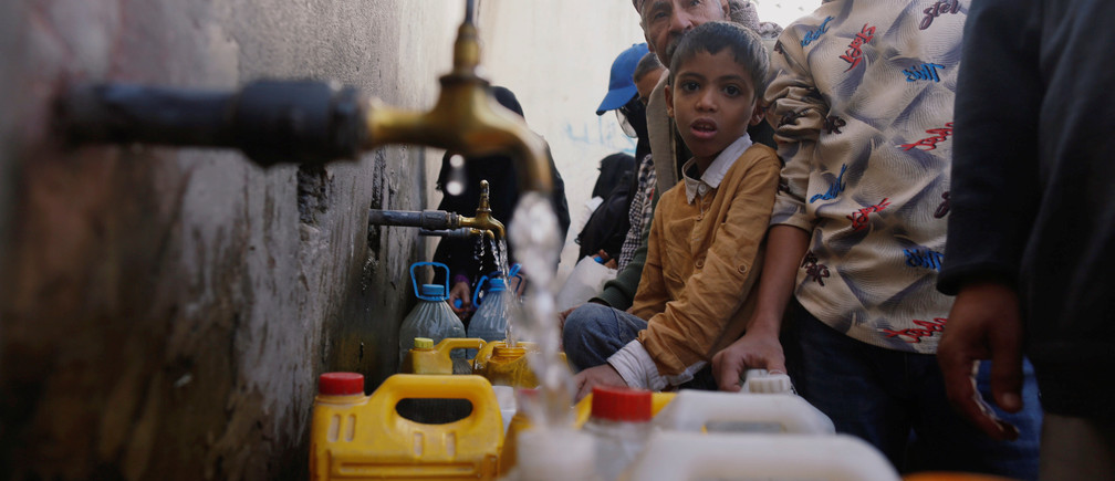 People collect drinking water from charity tap amid fears of a new cholera outbreak in Sanaa, Yemen November 5, 2018. Picture taken November 5, 2018. REUTERS/Khaled Abdullah - RC1E89B54FC0