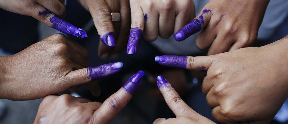 Venezuelans pose with their ink-stained fingers after voting for the successor of late President Hugo Chavez, in Caracas April 14, 2013. Venezuelans went to the polls to decide whether to honor Chavez's dying wish for a longtime loyalist to continue his hardline socialism or hand power to a young challenger vowing business-friendly changes. REUTERS/Tomas Bravo (VENEZUELA  - Tags: ELECTIONS POLITICS) - GM1E94E1SHB01