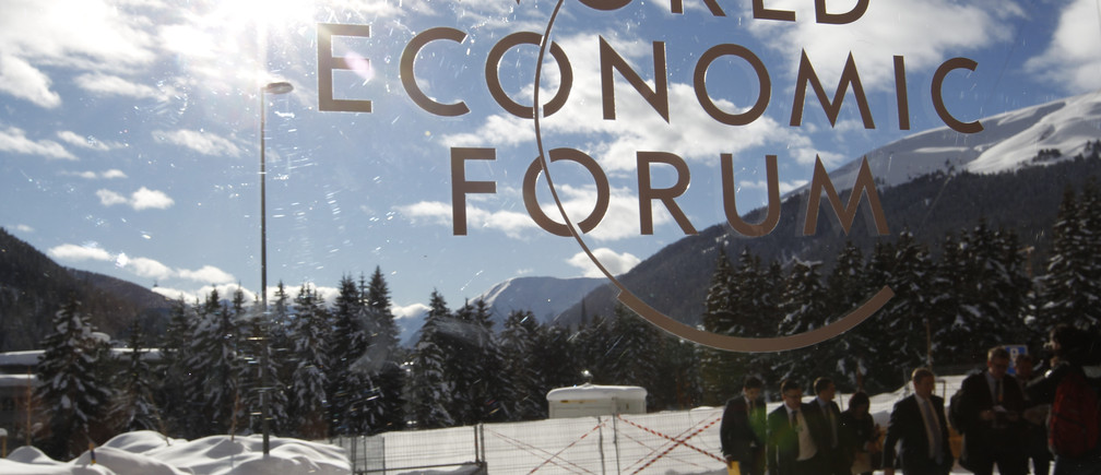 Visitors are reflected in window of the congress center, venue of the World Economic Forum (WEF) in Davos, January 26, 2012.                REUTERS/Arnd Wiegmann (SWITZERLAND  - Tags: POLITICS BUSINESS) - LR2E81Q14IV4T