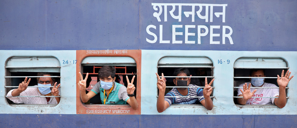 Migrant workers and pilgrims, who were stranded in the western state of Rajasthan due to a lockdown imposed by the government to prevent the spread of coronavirus disease (COVID-19), gesture from inside a train upon their arrival in their home state of eastern West Bengal, at a railway station on the outskirts of Kolkata, India, May 5, 2020. REUTERS/Rupak De Chowdhuri - RC27IG9107UV