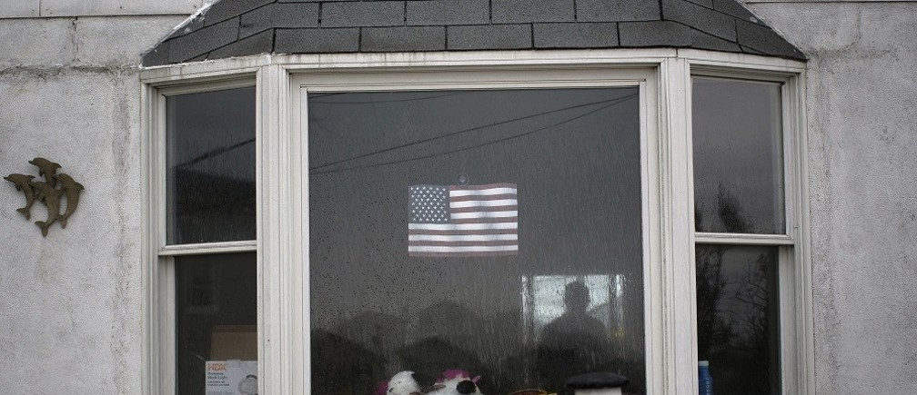 The silhouette of a man is seen inside a home in the Breezy Point section of the borough of Queens, six months after the landfall of Superstorm Sandy, in New York, April 29, 2013.  REUTERS/Shannon Stapleton (UNITED STATES - Tags: DISASTER ENVIRONMENT) - RTXZ3RM