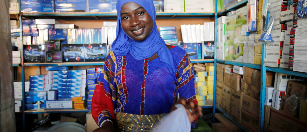 A woman smiles in her shop in Serekunda, Gambia December 3, 2016. REUTERS/ Thierry Gouegnon - RC119CBC8A50