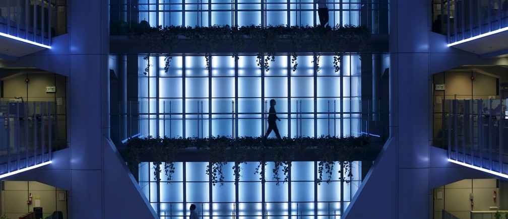 An office worker (top) talks on the mobile phone as others walk inside the HSBC headquarters in Hong Kong November 3, 2015.