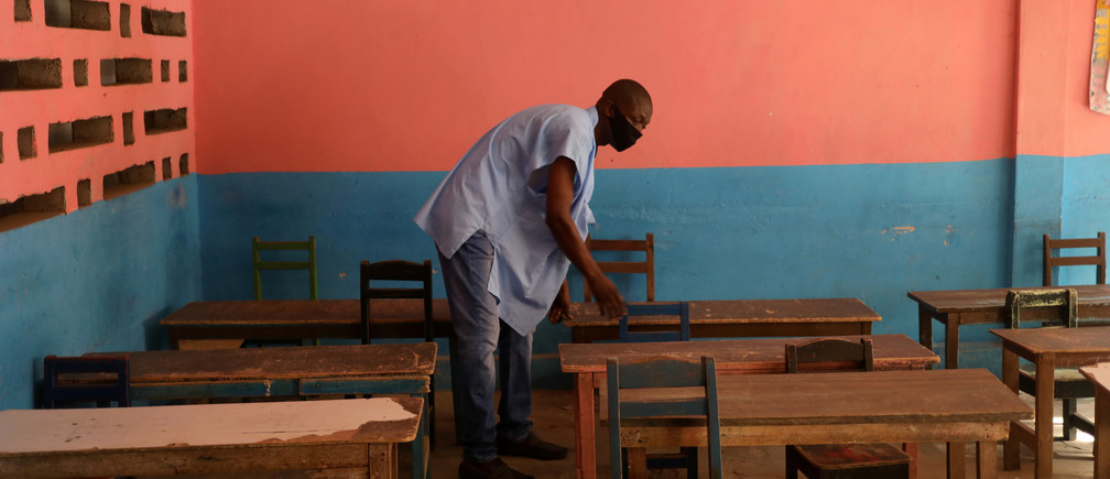 A teacher, wearing a protective mask, works in an empty classroom to maintain social distancing at the Merlan school of Paillet during the reopening of schools, as the lockdown due to coronavirus disease (COVID-19) is eased, in Abidjan, Ivory Coast May 25, 2020. REUTERS/Luc Gnago - RC2OVG9AHG9S