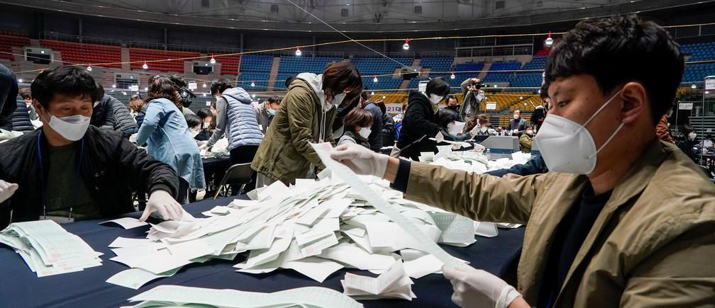 Funcionarios de la Comisión Electoral Nacional cuentan las papeletas para las elecciones parlamentarias, en medio del brote de la enfermedad coronavirus (COVID-19), en Seúl, Corea del Sur, el 15 de abril de 2020.