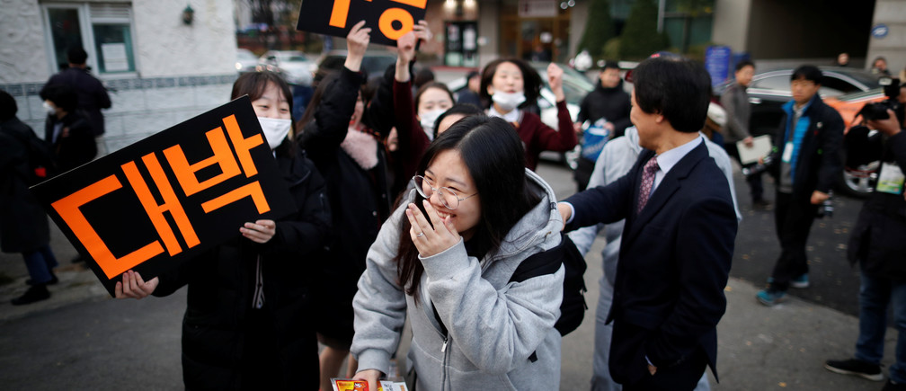 High school students cheer on a senior schoolmate (C) before she takes the annual college entrance examinations, in front of an exam hall in Seoul, South Korea, November 15, 2018.   REUTERS/Kim Hong-Ji - RC19B9097410