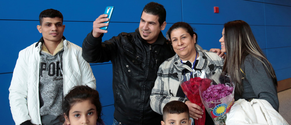 Iraqi refugee Amira Al-Qassab (2nd R) and four of her children are reunited with her son Rami as he uses his phone to Facetime the event to a relative as they arrive at Detroit Metro Airport in Romulus, Michigan, U.S. February 10, 2017. REUTERS/Rebecca Cook     TPX IMAGES OF THE DAY - RC182F7122E0