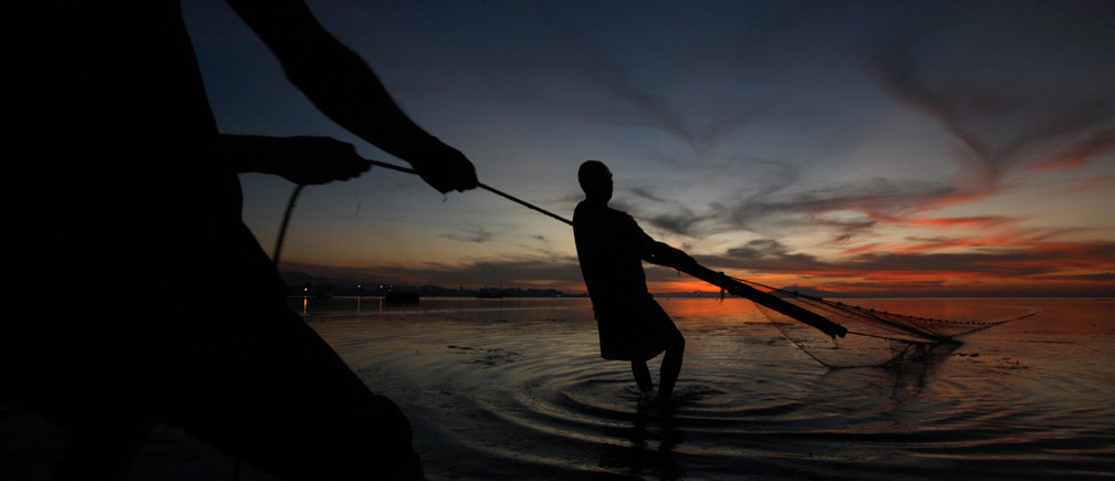 Fishermen pull in their net at sunset in Dili July 1, 2007.