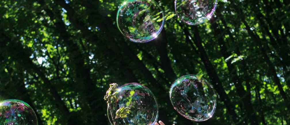 A child plays with soap bubbles at an event to support autistic children and their families in a park in Kiev May 28, 2013. The event, which was organised by several local charities, gave autistic children and their families the opportunity to spend a day in the park playing with soap bubbles as clowns and other performers entertained them. REUTERS/Gleb Garanich  (UKRAINE - Tags: SOCIETY HEALTH) - GM1E95S1NMQ01