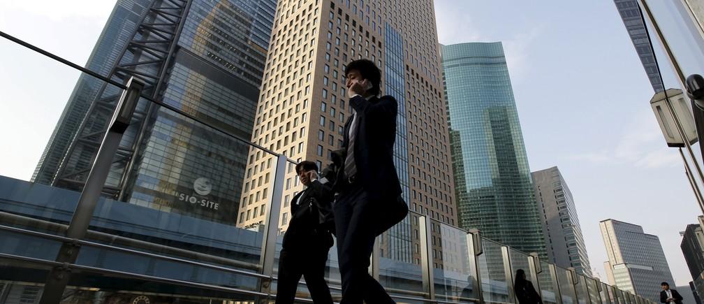 Businessmen walk in Tokyo's business district, Japan, March 23, 2016.
