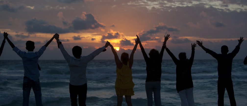 People raise their hands on a beach during the dawn of New Year's Day in Cancun January  1, 2012. REUTERS/Victor Ruiz Garcia (MEXICO - Tags: SOCIETY ANNIVERSARY) - GM1E8111SLL01