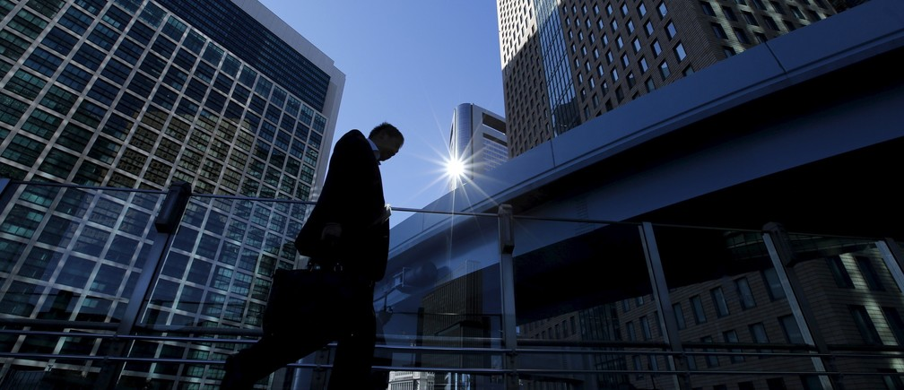 A businessman walks in Tokyo's business district, Japan January 20, 2016.