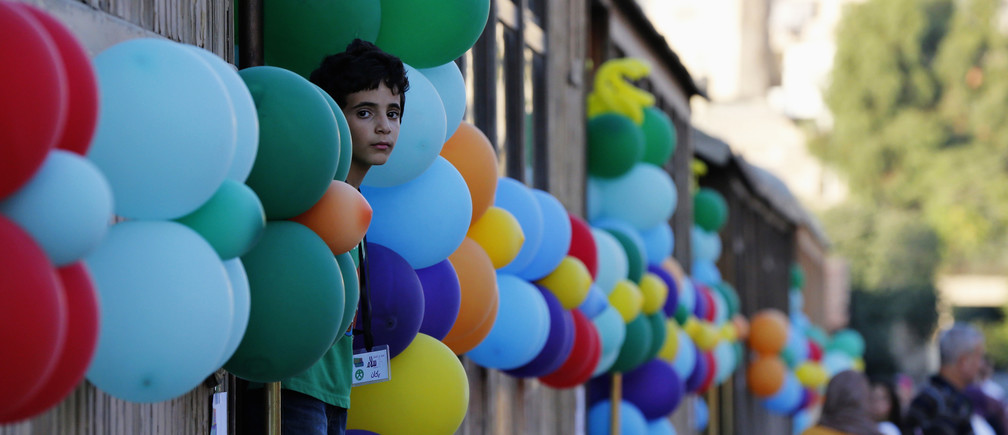 A boy looks out of a train before his meal for iftar, the breaking of fast meal, as he joins children from the Al-Baqaa Palestinian refugee camp during the Muslim fasting month of Ramadan in Amman July 7, 2014.