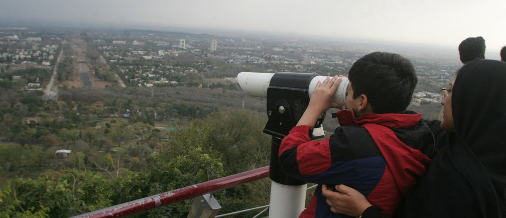 A boy looks out over the leafy Pakistani capital from a hillside viewing point in Islamabad March 4, 2007