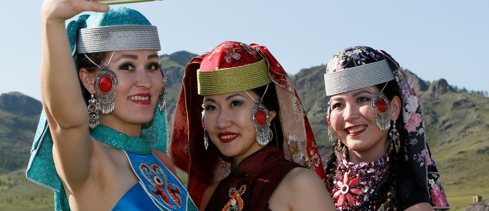 """Models of the """"Altyr"""" fashion theatre, dressed in Khakas national costumes, take a selfie during a break in a photo session, as a part of the rehearsal for the Tun-Pairam traditional holiday (The Holiday of the First Milk) celebration at a museum preserve outside Kazanovka village near Abakan in the Republic of Khakassia, Russia, May 28, 2016. The """"Khakas aal"""" (Khakas settlement) ethnographic complex demonstrates the model of a traditional local settlement of the 19th century based on local traditional wooden yurts. The museum preserve is located in a picturesque forest-steppe valley near the Abakan ridge of the Kuznetsk Alatau mountain range and displays numerous objects of the cultural and historical heritage of various epochs accumulated by the people living on this territory, according to representatives. REUTERS/Ilya Naymushin - D1BETGZSWUAB"""