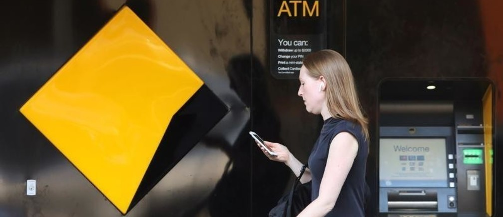 A woman walks past a Commonwealth Bank of Australia logo and ATM in Sydney, Australia, February 7, 2018. REUTERS/Daniel Munoz - RC1339AD7020