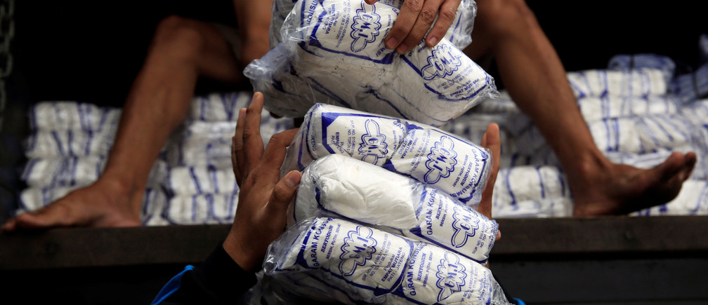 Workers unload packs of table salt from a truck at a warehouse in Jakarta, Indonesia, March 14, 2018. Picture taken March 14, 2018. REUTERS/Beawiharta - RC1ABB8C02F0