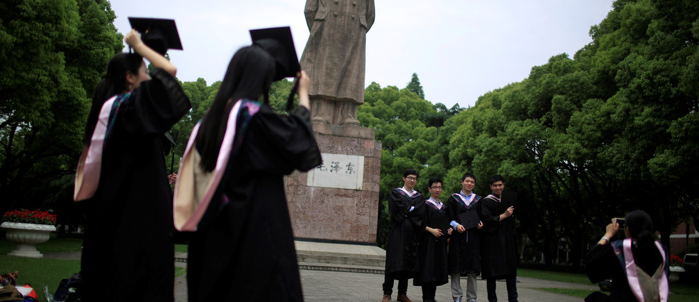 Graduates throw their mortar boards as they pose for pictures at Fudan University in Shanghai, China May 31, 2016.