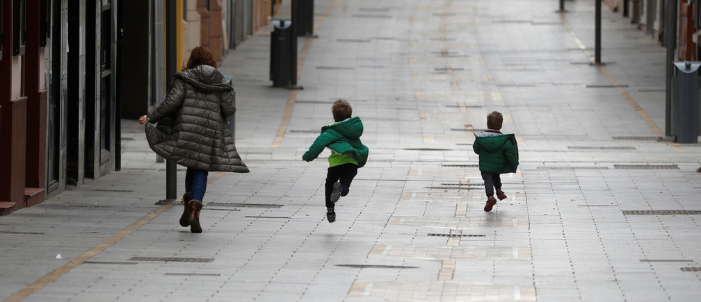 A woman and two children run along the empty La Bola street, after restrictions were partially lifted for children for the first time in six weeks, during the coronavirus disease (COVID-19) outbreak in Ronda, Spain, April 26, 2020. REUTERS/Jon Nazca - RC2ECG915UQL