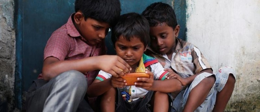 Children play a game on a mobile phone at slum area in New Delhi, India July 4, 2017. REUTERS/Adnan Abidi - RTX3A0MM