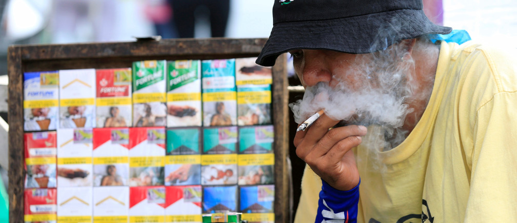 A vendor smokes beside his cigarette stall, while waiting along a main street, in metro Manila, Philippines May 19, 2017. REUTERS/Romeo Ranoco - RC1D5C8E8790