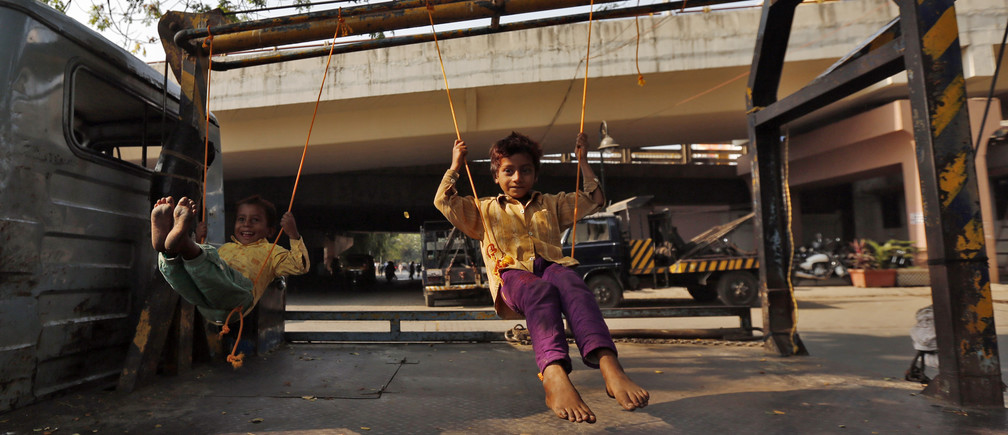 Children play on improvised swings on a tow truck parked on a roadside in Mumbai March 24, 2014. REUTERS/Mansi Thapliyal (INDIA - Tags: SOCIETY) - RTR3IBMP