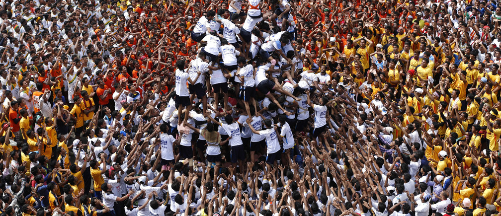 Devotees try to form a human pyramid to break a clay pot containing curd during the celebrations to mark the Hindu festival of Janmashtami in Mumbai August 18, 2014. Janmashtami, which marks the birthday of Hindu god Krishna, is being celebrated across the country today. REUTERS/Shailesh Andrade (INDIA - Tags: RELIGION TPX IMAGES OF THE DAY)         FOR BEST QUALITY IMAGE ALSO SEE: GF2EAAD0ALF01 - GM1EA8I1UMN01