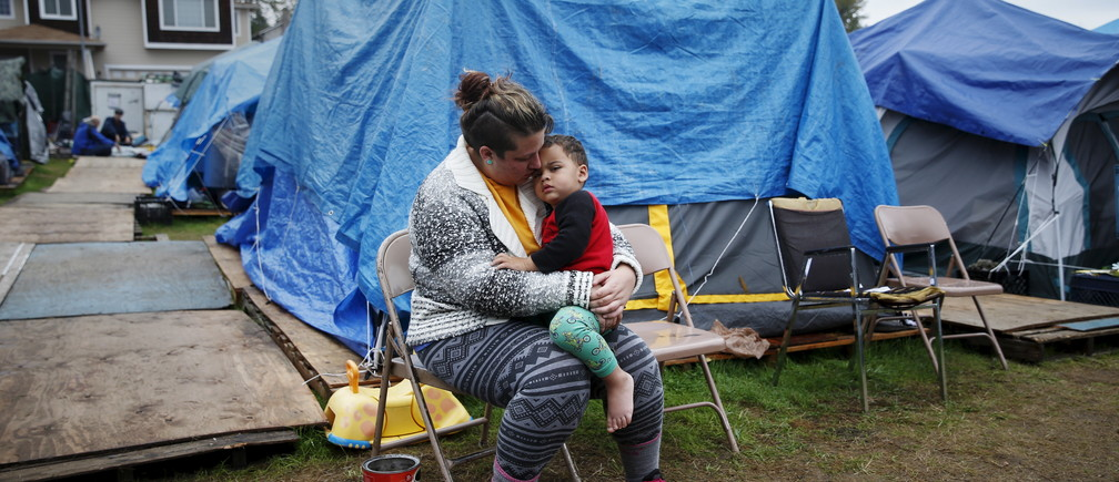 """Kadee Ingram, 28, holds her son Sean, 2, at SHARE/WHEEL Tent City 3 outside Seattle, Washington October 13, 2015. Ingram lost her job, and soon afterwards her partner Renee lost her job. """"It got (to) the point where we couldn't get a job fast enough and we lost our apartment,"""" Ingram said. """"Coming here, we really like it, being outside especially, we feel safe. We wish we would have known about it sooner.""""  REUTERS/Shannon Stapleton PICTURE 17 OF 35 - SEARCH """"STAPLETON TENTS"""" FOR ALL IMAGES TPX IMAGES OF THE DAY      TPX IMAGES OF THE DAY      - RTX1Z3JC"""