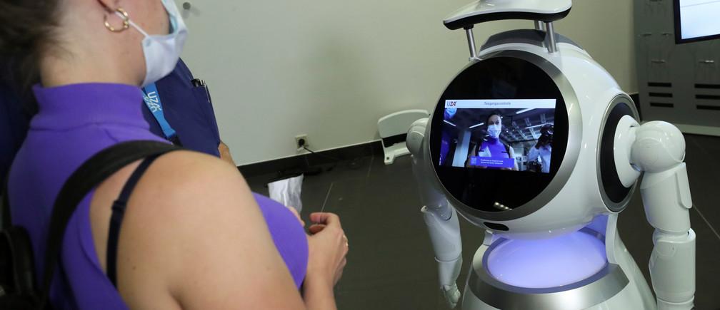 Un visitante del Hospital Universitario de Amberes (UZA) interactúa con un robot llamado CRUZR, puesto a disposición de los hospitales y otros lugares por la empresa belga ZoraBots para controlar la temperatura y el buen posicionamiento de la máscara facial protectora, en medio del brote de la enfermedad coronavirus (COVID-19), en Amberes, Bélgica, el 29 de mayo de 2020.